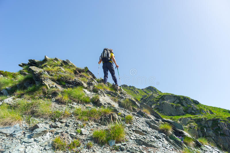 Mountain climbing on steep rocky slope. One backpacker hiking uphill on steep rocky slope towards the mountain summit. Concept of reaching the goal and stock photography