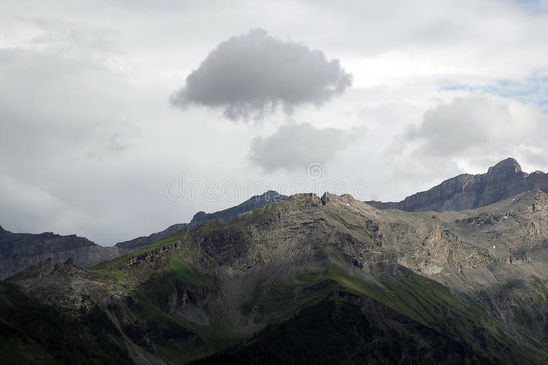 Mountain And Cloud. A small cloud hovering over a mountain peak royalty free stock photo
