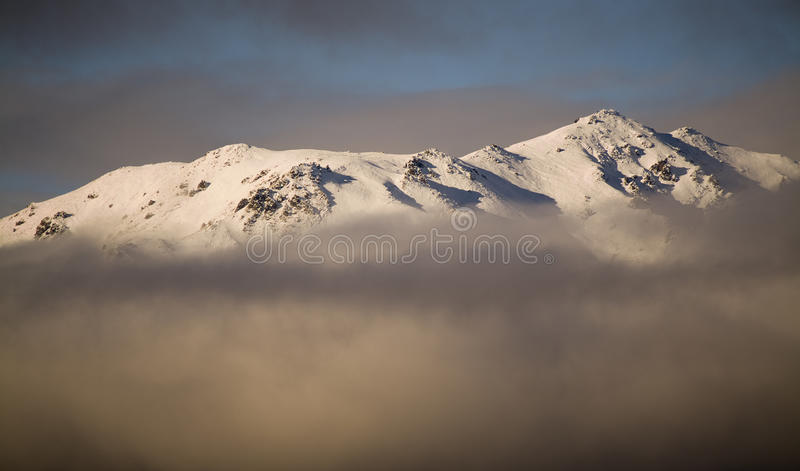 Mountain Clouds. South Island, New Zealand. The tip of a mountain peaks through the clouds royalty free stock photo