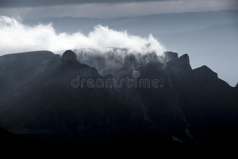 Mountain clouds at sunset, above high peaks. Nature is preparing for the night stock image