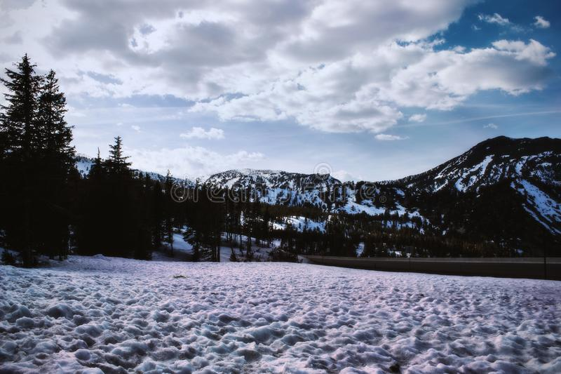 Mountain Covered by Snow Under White Clouds and Blue Sky royalty free stock photos