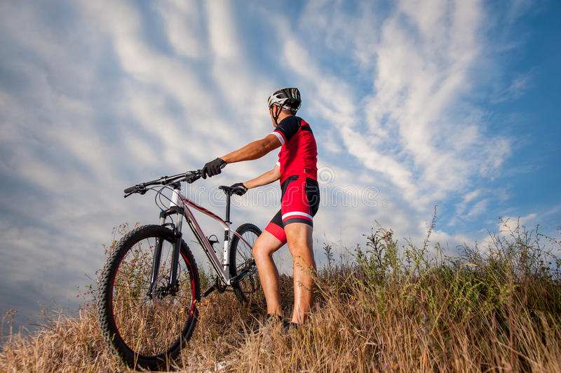 Mountain cyclist resting with his bike against blue sky. Mountain Bike cyclist in red sportswear and helmet resting with his bike against blue sky. Biker is stock images