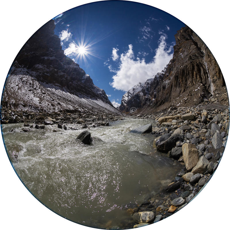 Mountain gorge and river in Himalayas. Mountain gorge in Himalayas near the headwaters of Myagdi Khola river, Nepal. The stream flows on stone bed among steep stock photo
