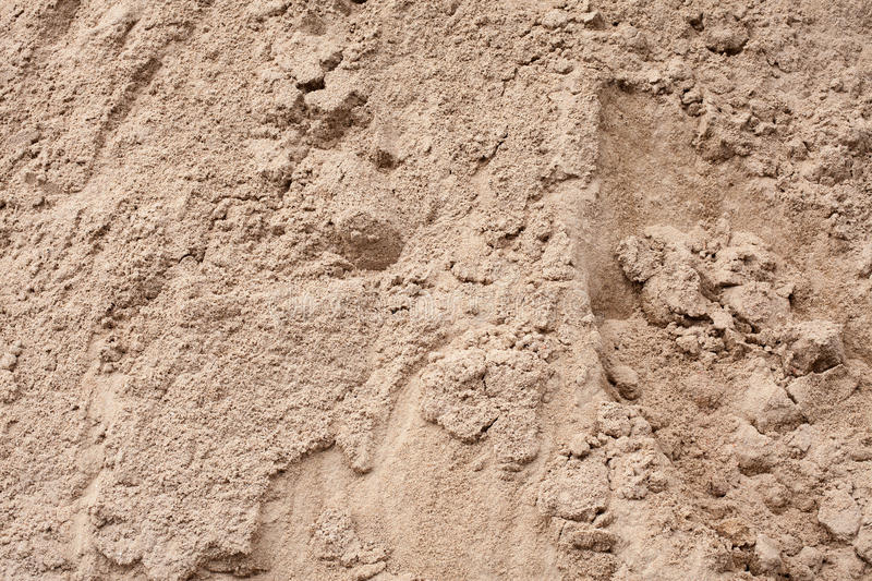Mountain gray-brown construction sand. Close-up. Textural background royalty free stock photography