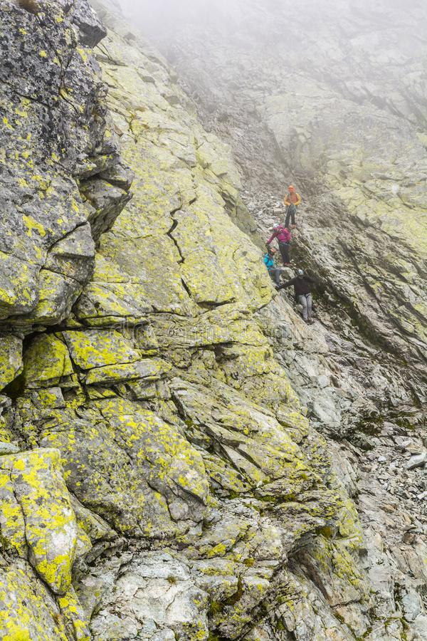 A mountain guide bringing customers to the gully after climbing the summit - Wysoka Vysoka stock photography