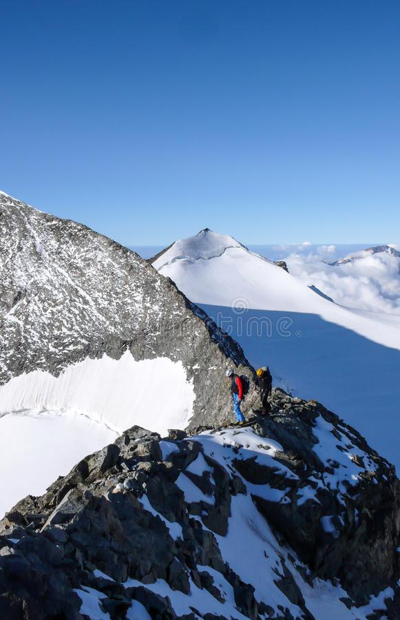 Mountain guide and client on a rocky ridge on their way to a high alpine peak with a great view behind them. A mountain guide and client on a rocky ridge on stock image