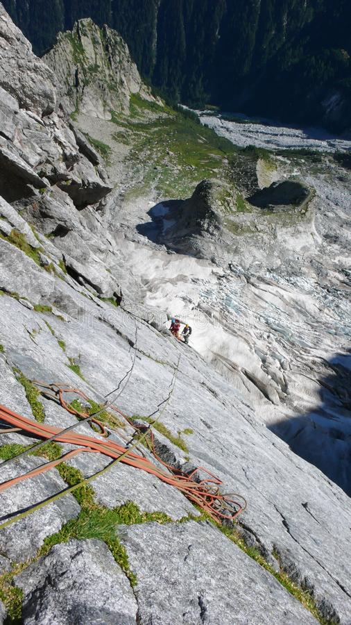 Mountain guide on a hard granite climb to a high alpine peak in the Swiss Alps stock images