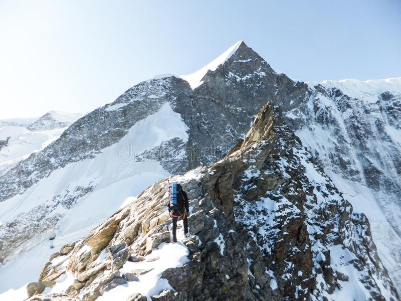 Mountain guide heads towards the summit of a high alpine peak as he climbs an exposed rocky ridge. A mountain guide heads towards the summit of a high alpine stock photo