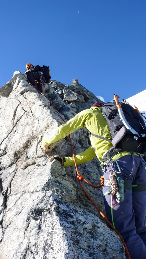 Mountain guide leading male client to the summit of a high alpine peak on a beautiful summer day. Near Pontresina in the Swiss Alps stock image