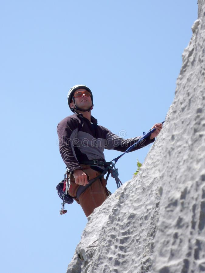 Male mountain climber on a steep rock climbing route in the Swiss Alps near Klosters. Mountain guide rock climbing in the Alps of Switzerland in the Raetikon stock images