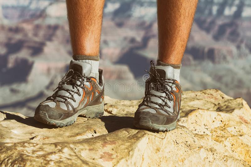 Mountain hike man hiker trekking travel walking with hiking shoes closeup of feet standing. On rock royalty free stock image