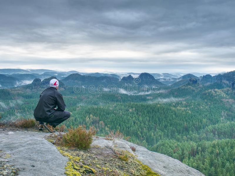 Mountain hiker looking into moody misty landscape. Rear view stock photo