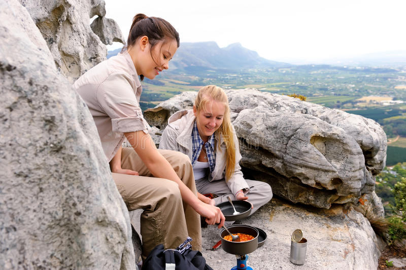 Mountain hikers cook food. Two women cook some hiking food on a gas stove while sitting on top of a mountain royalty free stock images
