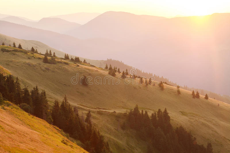 Mountain hills in background of the rays of rising sun. Mountain hills in the background of the rays of rising sun stock photo