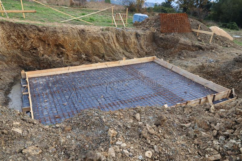Mountain home construction. Leveled ground with prepared reinforced concrete foundation royalty free stock photos