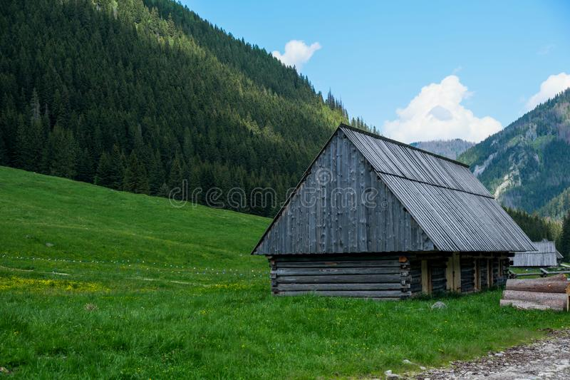 Mountain house by the road. Wooden house in colorful field stock photo