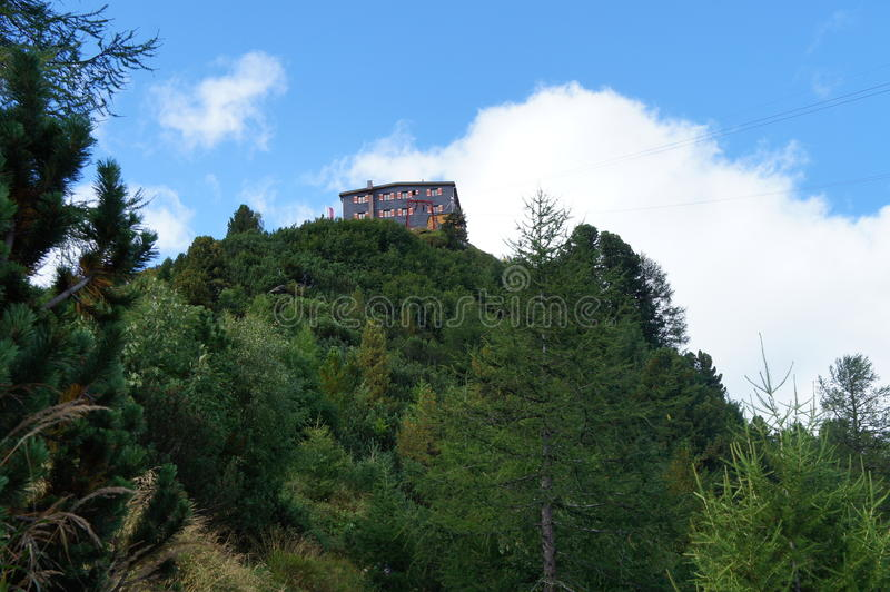 Mountain house in the Stubai Alps. In Tyrol, Austria, view from the frog perspective; wooded mountain, blue sky with white clouds stock photography