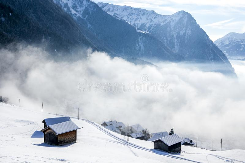 Mountain houses and clouds between the mountains in the Alps on a Sunny day royalty free stock photography