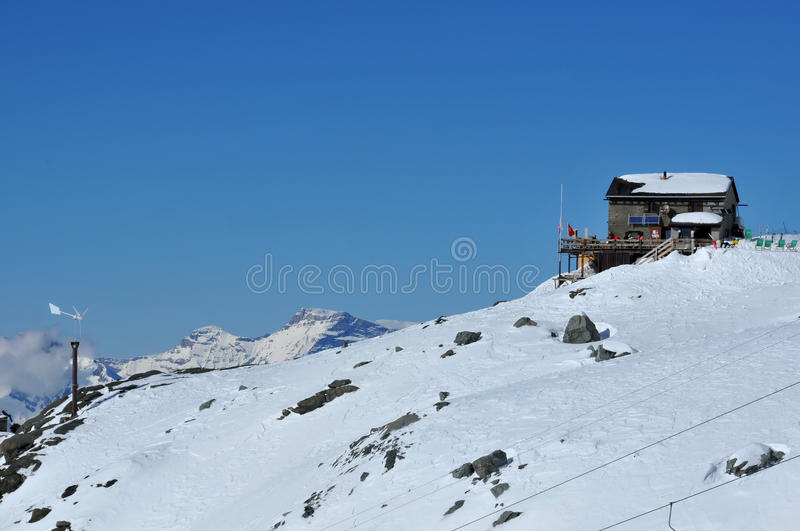 Mountain hut. Self sufficient mountain hut for skiers with solar cells and wind generator for its electricity needs stock photo