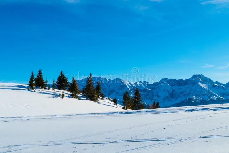 Mountain with hut in the snow in the alps stock photography