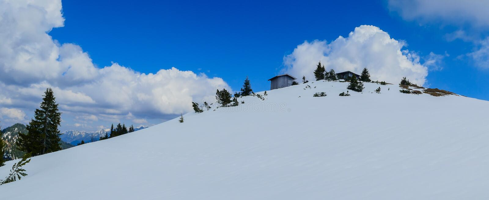 Mountain with hut in the snow in the alps royalty free stock photo