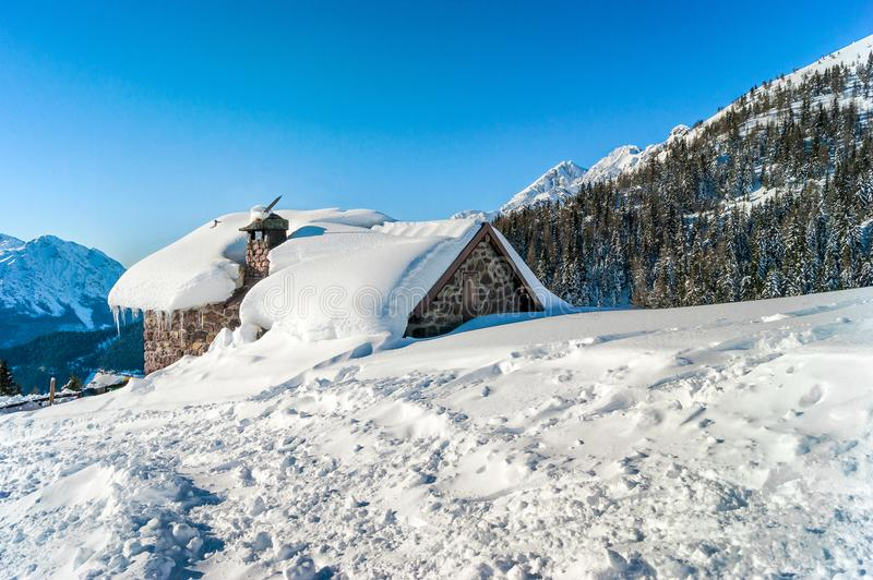 Mountain hut in the snow royalty free stock photography