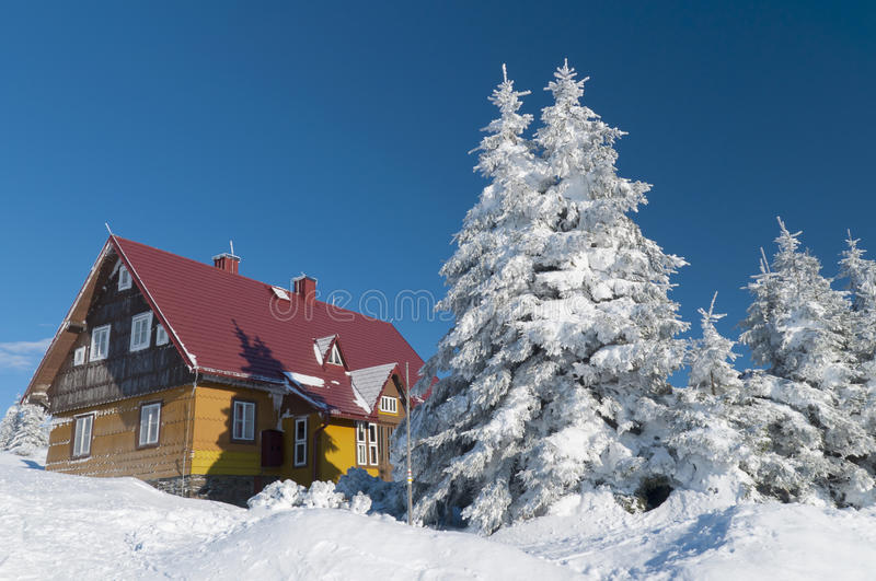 Mountain hut in winter stock photography