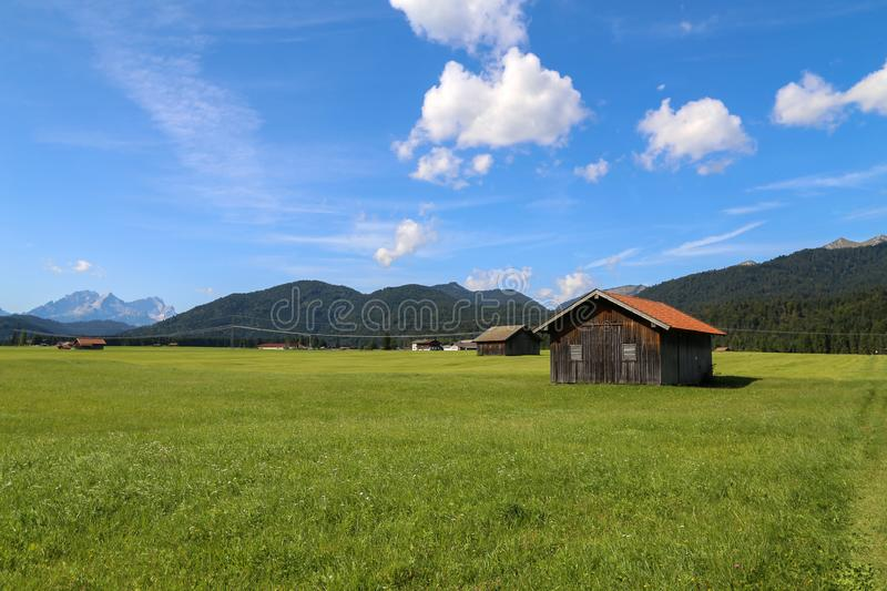 Mountain huts on green meadows in the Alps. Mountain huts on green meadows in summer in the Alps royalty free stock photos