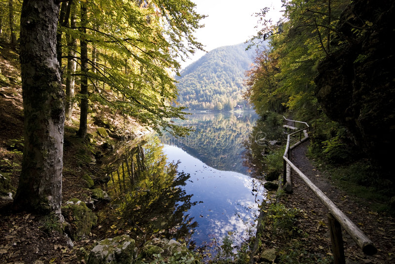 Mountain Lake. With handrail, trees and reflection from lower lake in Fusine - Tarvisio, Italy 2007 royalty free stock images