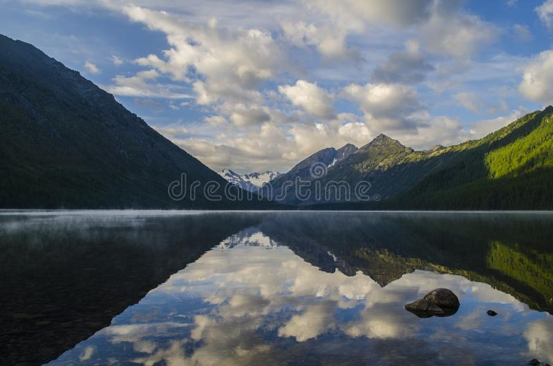 Mountain lake in the Altai. A serene morning at a mountain lake in the Altai stock images