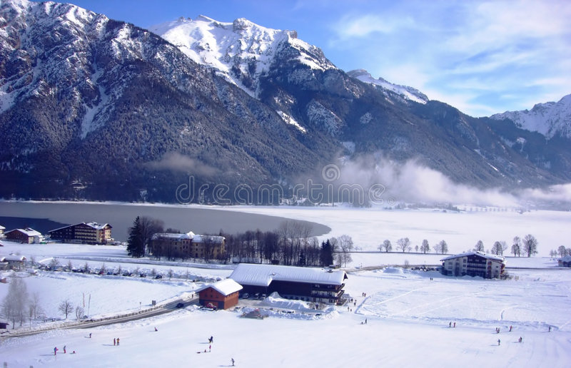 Mountain lake and chalets. Overview of mountain lake with white cloud, distant skiers and mountain backdrop stock images