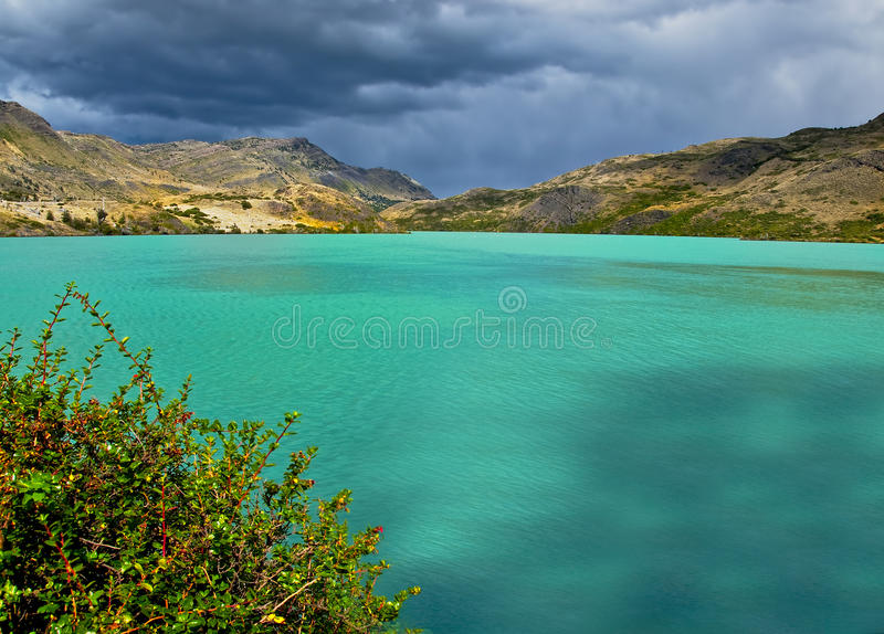 Mountain Lake, Chile. The turquoise blue waters of Lake Pehoe in Torres del Paine National Park, in the Andes mountains of southern Patagonia, Chile, with dark royalty free stock photo