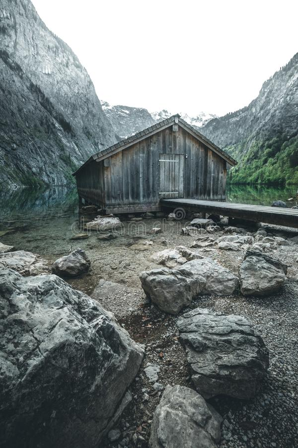 Mountain lake mountain lake with dock and boat house. At obersee in germany during autumn stock images