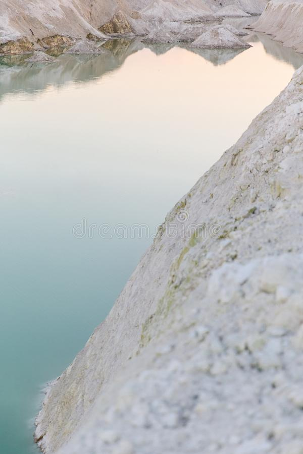Mountain lake with emerald water at sunset. Chalky quarries - emerald blue water, vanilla sunset, white stones, pink sunset royalty free stock image