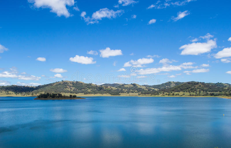 Blue calm deep water lake with small island surrounded by hills with trees under a blue sky with small soft white clouds. Blue calm deep water lake with small stock photography