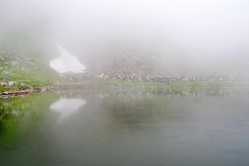 Fog over the small mountain lake Fuscher Lacke on the Grossglockner High Alpine Road. royalty free stock photos