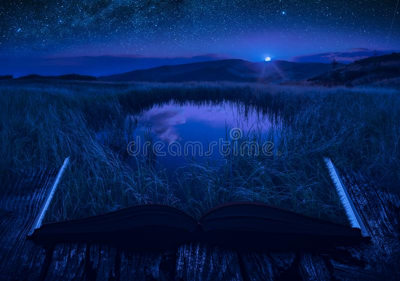 Mountain lake in a moon light on the pages of an open book stock images