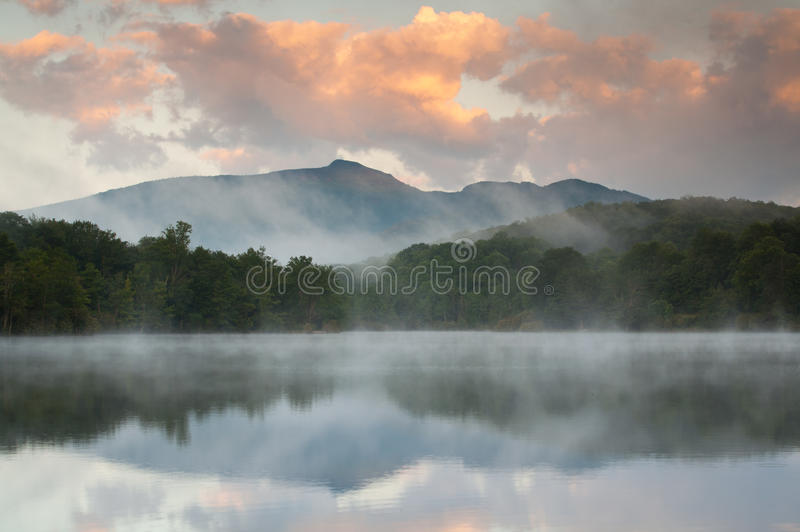 Mountain Lake Reflection off Blue Ridge Parkway. Grandfather Mountain, a Southern Appalachian Blue Ridge mountain, reflects in the calm, foggy waters of Price stock images