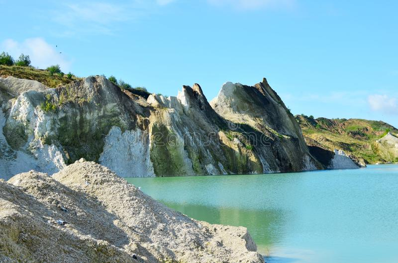 Mountain lake or river with a turquoise or blue tint of water in a rock canyon at Krasnoselsky village in the Belarus. Industrial mining quarry for the stock photos