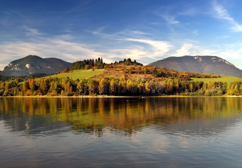 Mountain lake shoreline. Peaceful, quiet mountain lake shoreline with fall foliage stock images