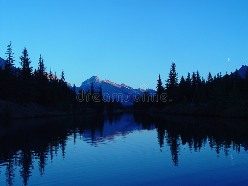 Mountain lake at sunset. Moon in sky above, mountains reflected in lake, in the Canadian Rockies royalty free stock photo
