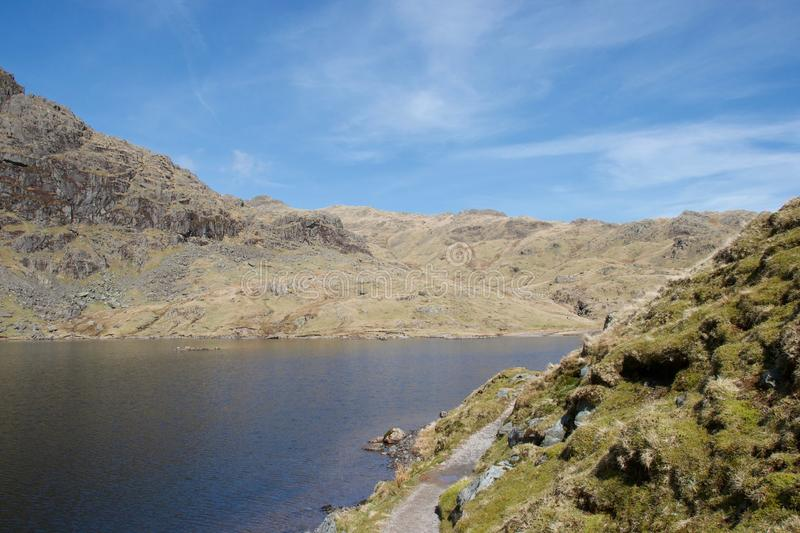 Mountain lake tarn and crags in English Lake District. Footpath in foreground, round a clear blue mountain lake tarn nestled between craggy, grey, rocky cliffs stock photos