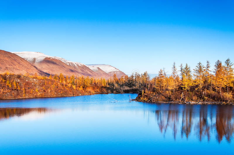 Mountain lake in tundra, deep autumn in the Taimyr Peninsula near Norilsk. In the distance can be seen the mountain plateau reserve Putorana royalty free stock photo