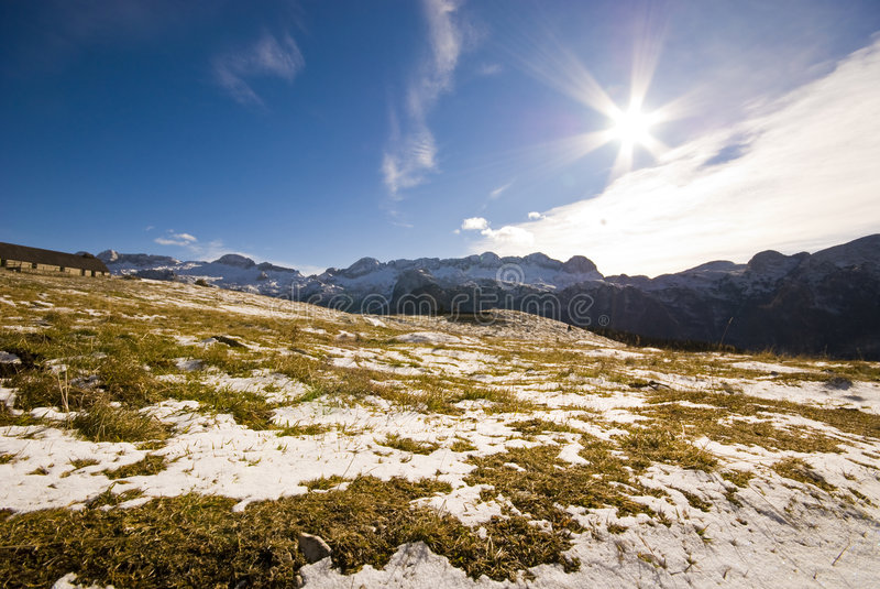 Mountain Landscape. Spring mountain landscape with yellow grass, snow and a sunstar in a sunny day - shot from an ultra wide angle - Malghe del Montasio - Italy royalty free stock image