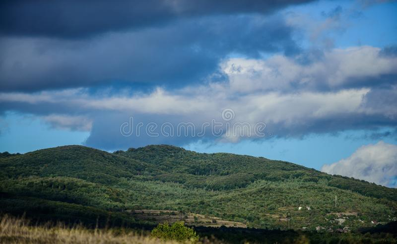 Mountain landscape. blue sky with rainy clouds. sunny weather. travel and wanderlust. adventures are waiting for you royalty free stock photography