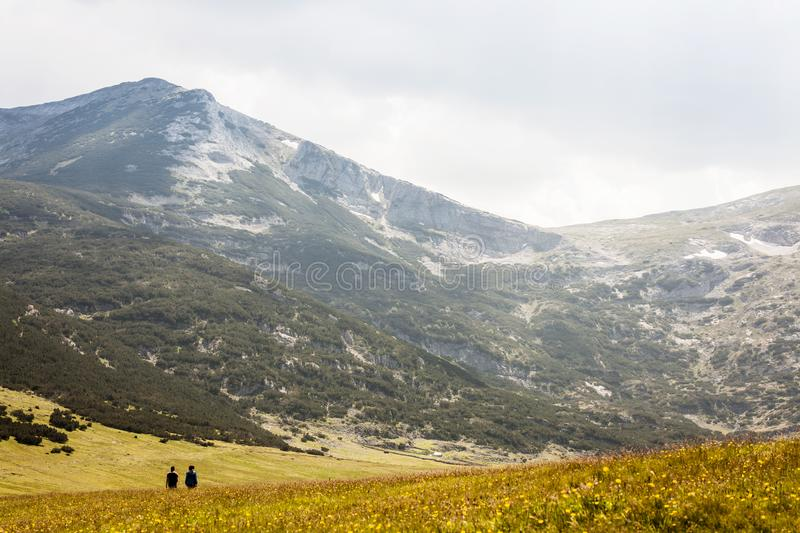 Mountain landscape with couple of silhouette hikers. Silhouette hikers couple on a field in the mountains stock image