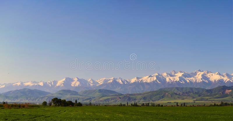 Mountain landscape. Fresh green meadows at sunrise in springtime, mountains lit by the rising sun. Panoramic view of the idyllic mountain landscape. Fresh green stock photography