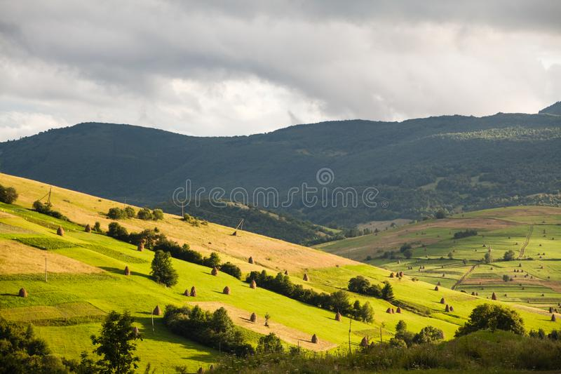 Mountain landscape with green and yellow grass and haystacks stock images