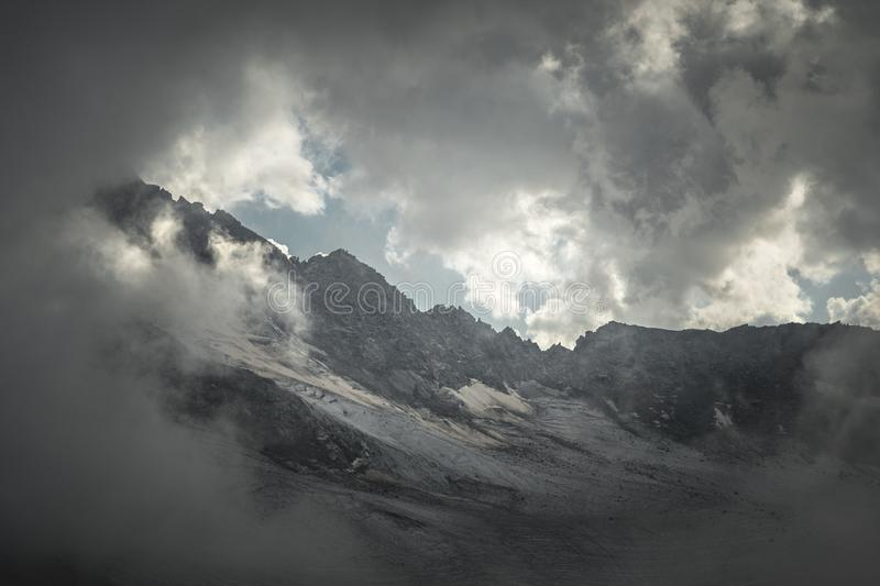 Mountain landscape of a high mountain slope with a cracked glacier muddy volcanic slope against the backdrop of the royalty free stock images