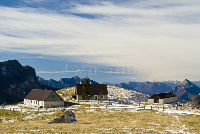 Mountain Landscape with houses. Spring mountain landscape with yellow grass, snow, pines and building in a sunny day - Malghe del Montasio - Italy 2007 stock photos